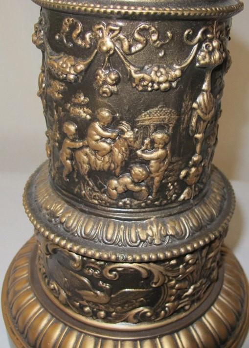 Antique lamp with high relief scene frolicking cherubs, birds, goats